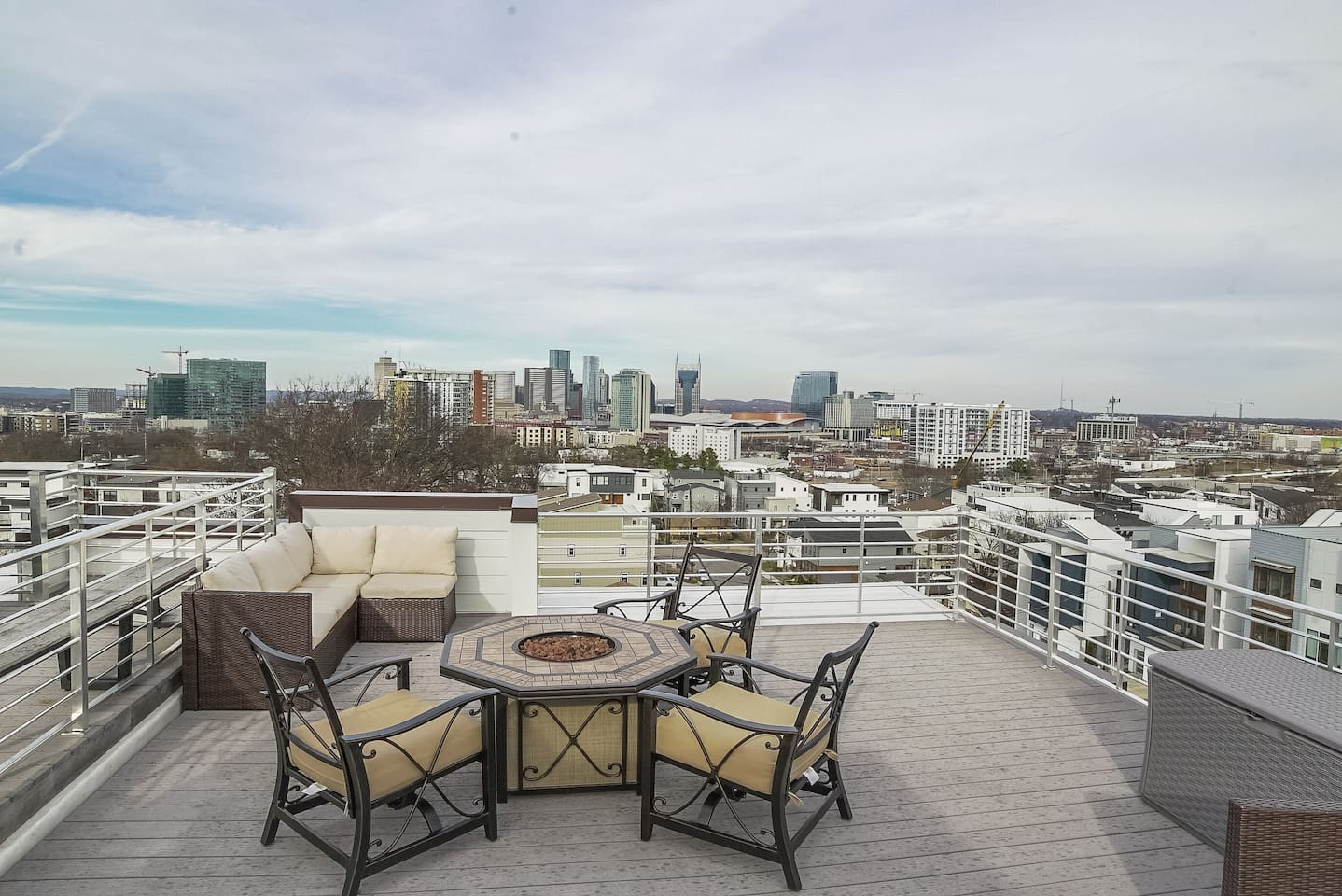 Lots of space on this roof top deck with couch and fire pit while looking at the downtown Nashville skyline and the iconic Batman building.