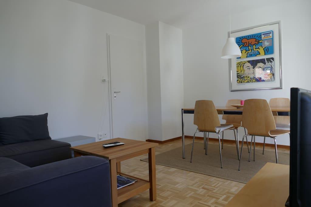 Wohn-, Esszimmer mit Ecksofa (ausziehbar für Bett), Coffee Table, Ausgang zum grossen Balkon West, USM Esstisch für mind. 4 Personen, TV, Internet