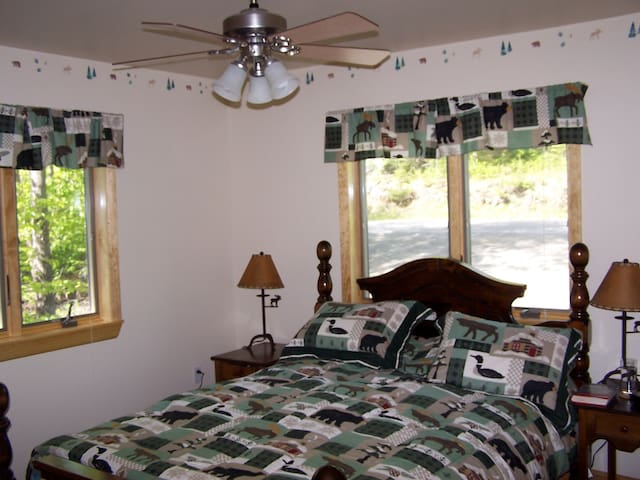 MASTER BEDROOM with north woods decor and a huge topo map to plan out your daily hikes.