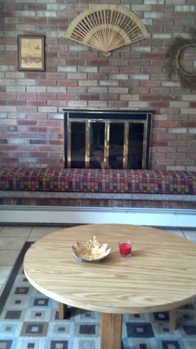 Brick living room wall. Romantic fireplace. Wood provided. Cushion removable. Clean gas-powered hot water baseboard heat.