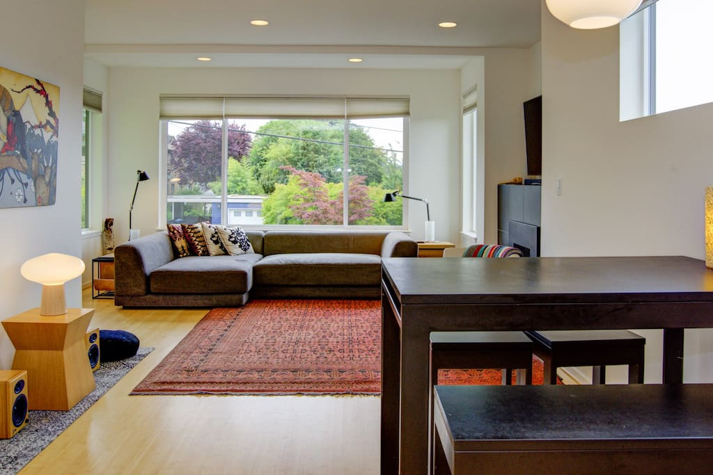Cozy living room with fireplace and bright, south facing windows with view of Ballard, Olympic Mountains and the sunset
