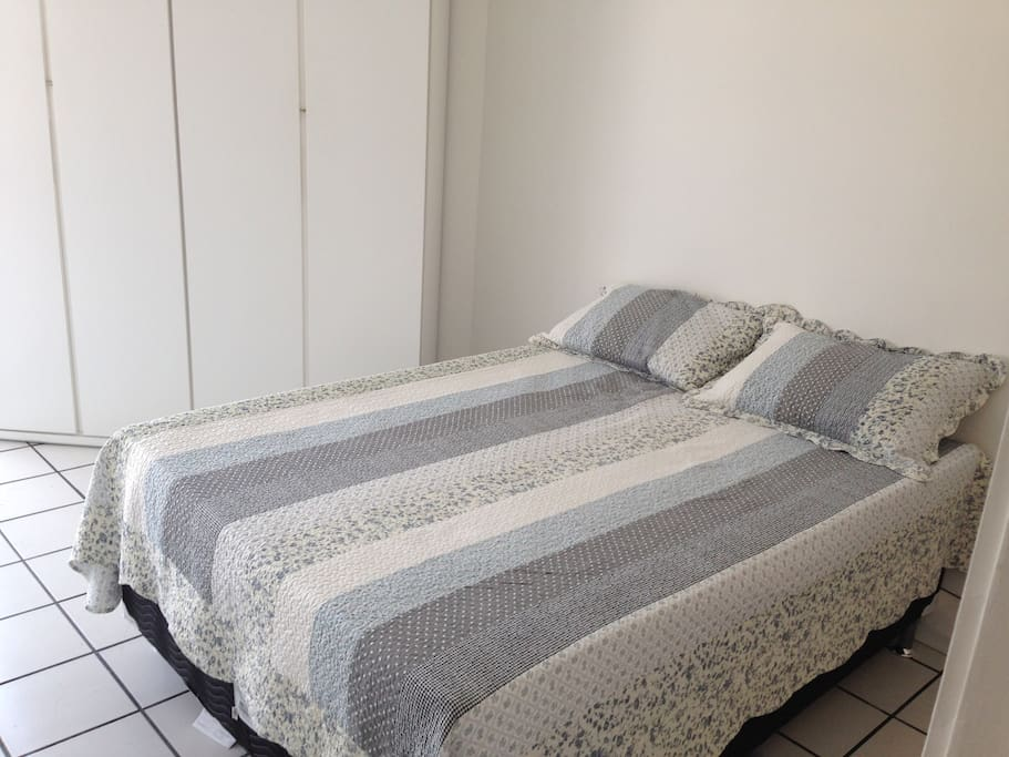Quarto com cama de casal e armário.