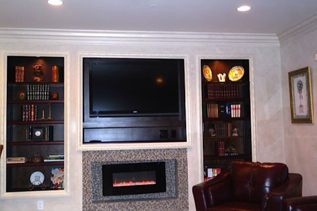 Built in media center featuring recessed lights literature a large flat screen with cable. Heat generating Eco friendly fireplace.