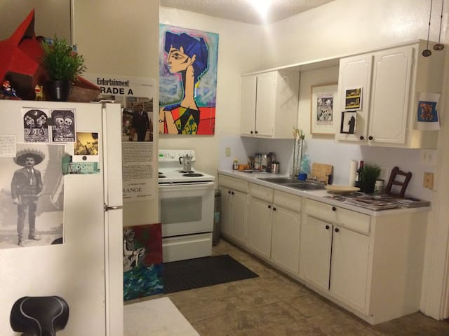 Roomy kitchen with cooking ware.