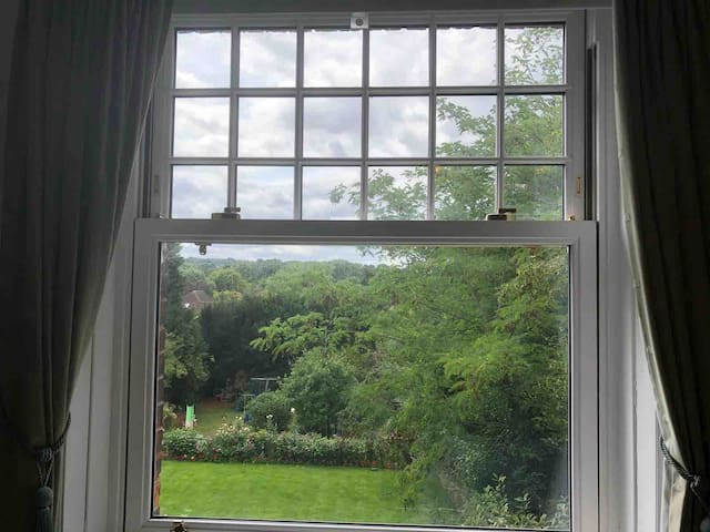 The room looks out onto a beautiful green garden