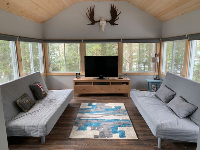 And the tv room has two futons that pull out to double size beds. This room is surrounded by windows, giving you a 180 view of the lake and trees.