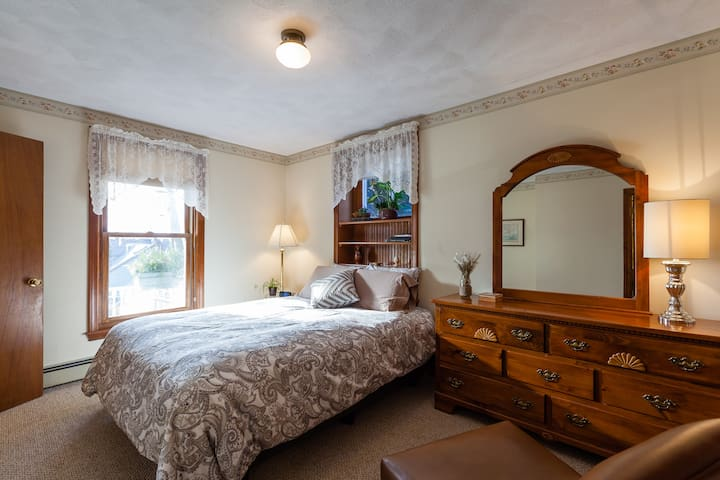 Bedroom with bureau and Queen bed with down-filled duvet. In warmer months the duvet is replaced with a lighter weight ivory matelasse.