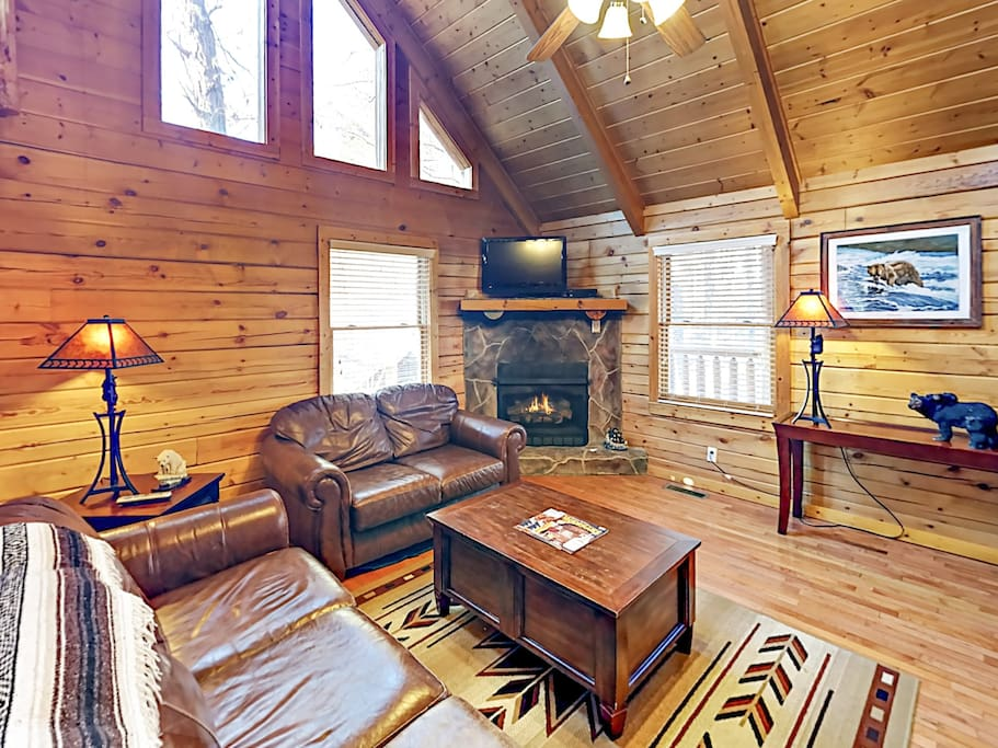 Relax in style in the warm-hued living room, outfitted with a flat screen TV and fireplace.