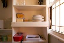 Microwave, fridge, kettle, toaster, cutlery, plates, bowls.