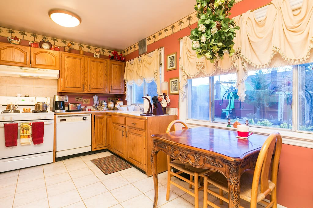 Our kitchen which has a very colorful warm ambiance with a fully functional microwave, oven, toaster, sink, and stoves.