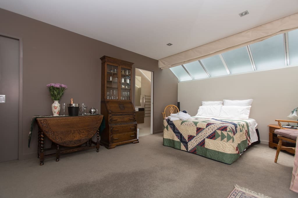Comfortable bed, bureau and in room dining table. Door to en-suite on the right and door to walk-in wardrobe on the left