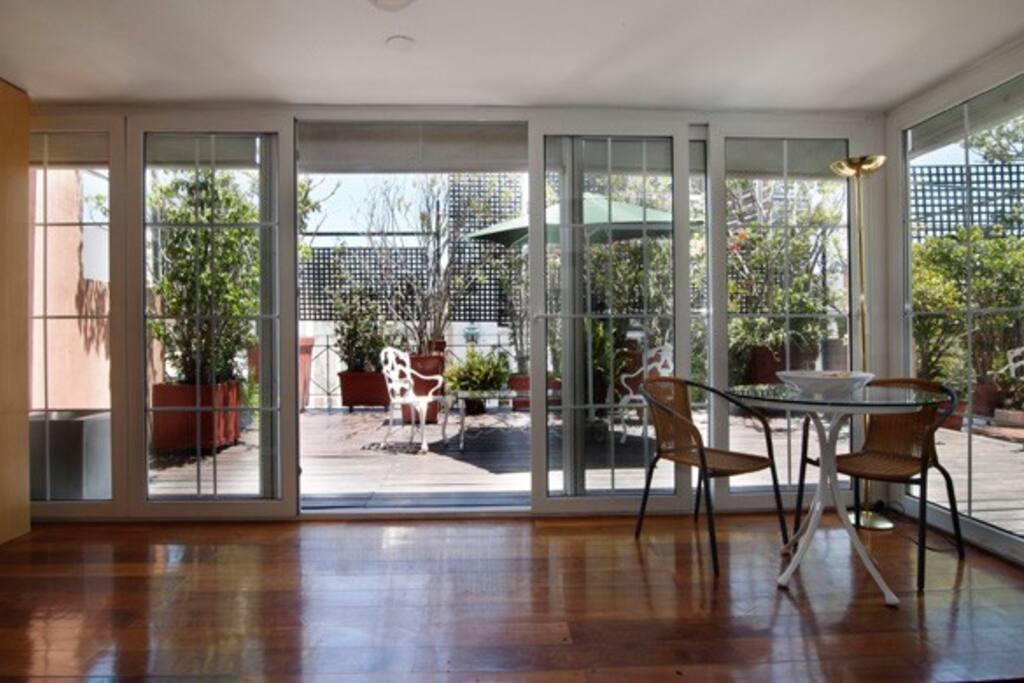 El ambiente único tiene vista y salida a la terraza a través de puertas- ventanas amplias per permiten ventilar e iluminar todo el departamento.