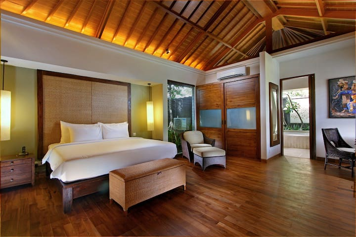 master bedroom with king size bed, work desk, sofa and overlooking to the pool.