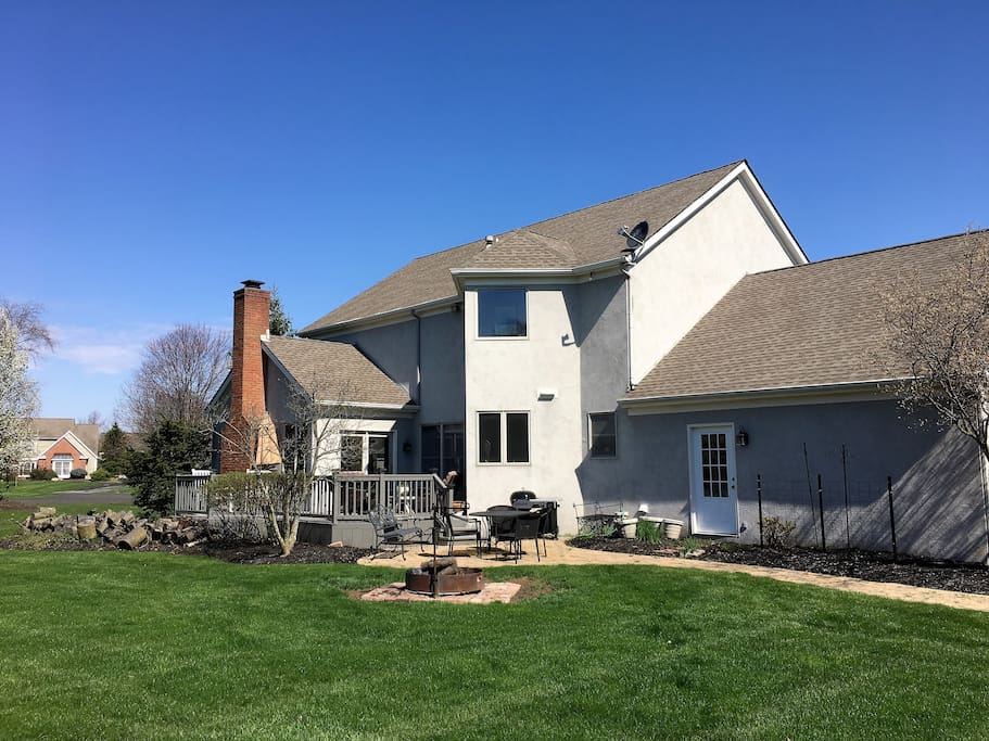Back of home with large deck with plenty of furniture, dining set on paver patio and charcoal grill, and firepit!