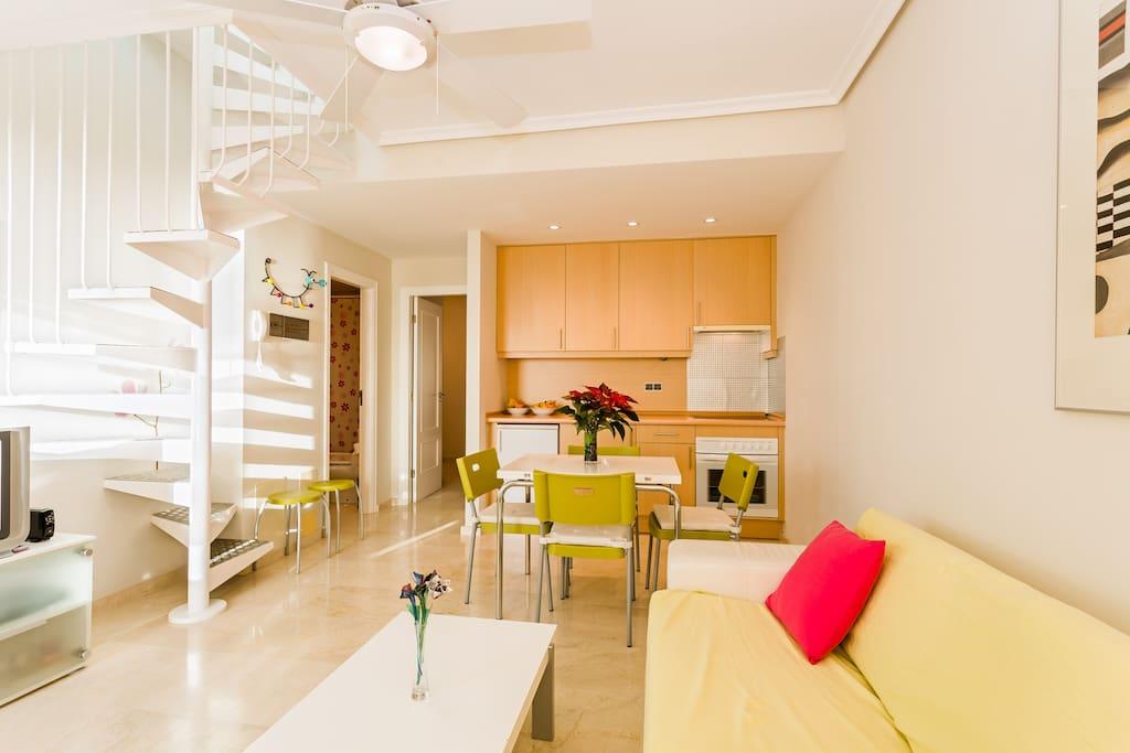 Salón y cocina americana con escalera de caracol que da acceso a la planta superior