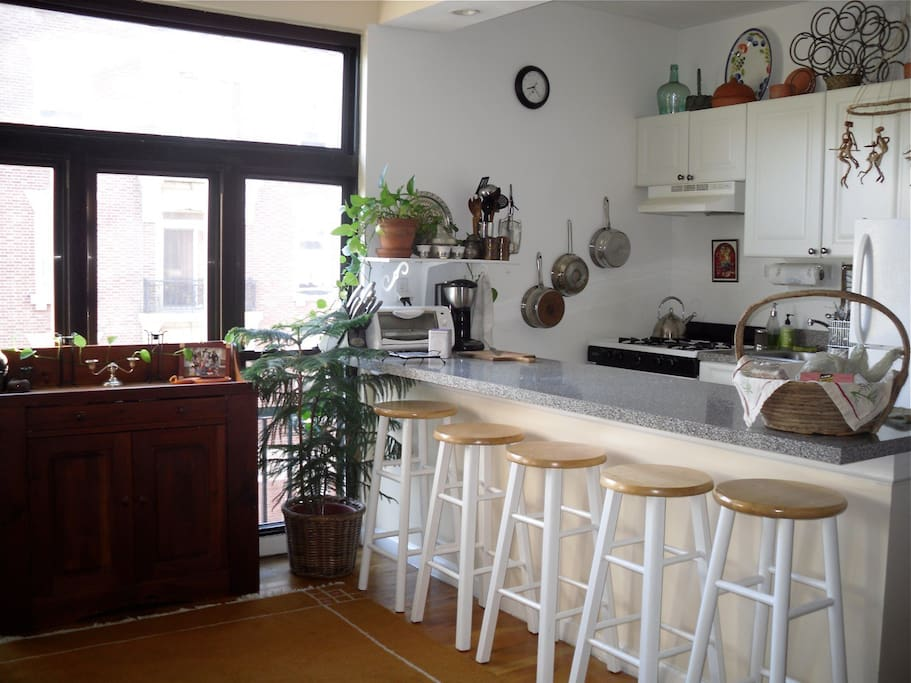 The kitchen looks out on the open plan living room and the Hudson river.