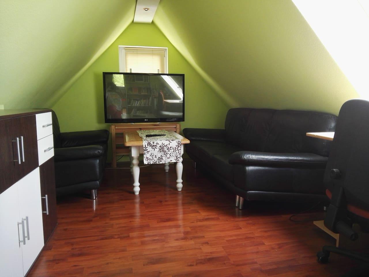 Wohnbereich mit TV und Sitzecke sowie Schreibtisch