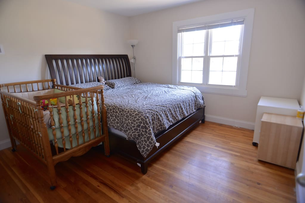 Spacious bedroom with king size bed and crib for kid