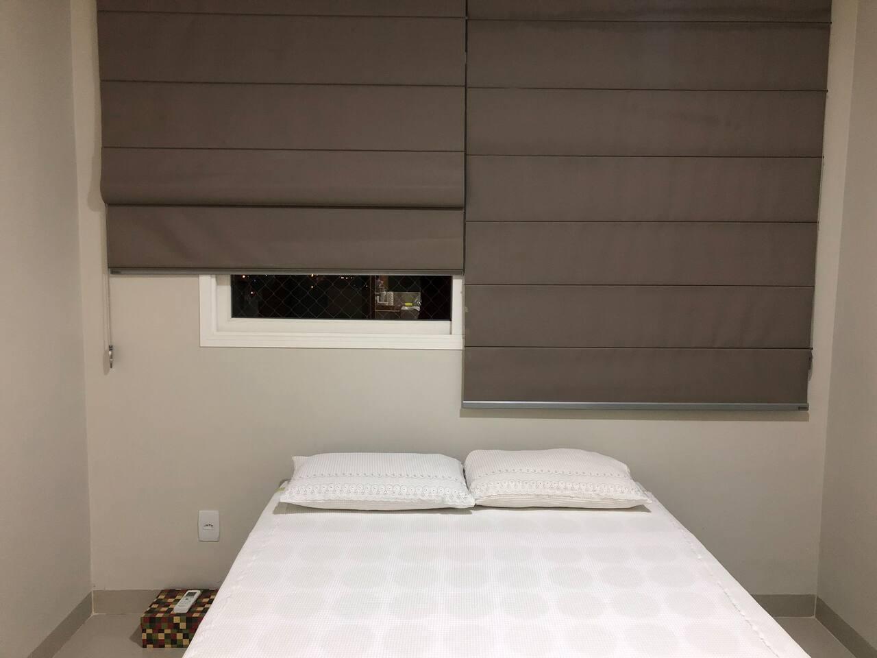 Suite com cama box de casal, cortina blackout, edredons, roupa de banho, mesa de apoio e aparelho de ar condicionado.