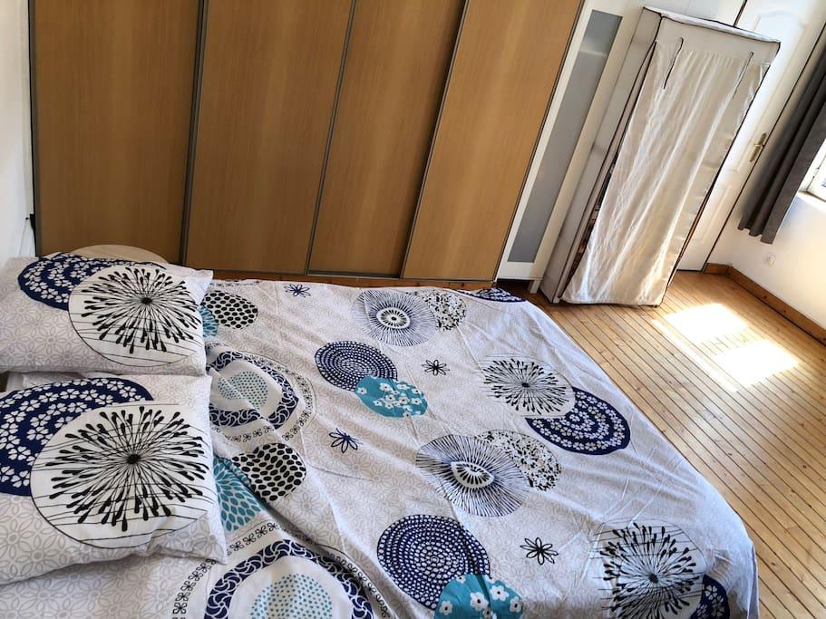 Chambre avec un lit deux places, dressing, et tv
