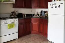 Fully equipped kitchen with big fridge, microwave, toaster and coffee maker.