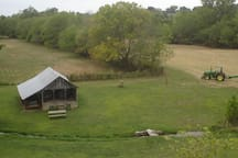 "A summertime view from the garden into the Finley River valley and the ""Music Barn"" amphitheater. A cool spring branch can be seen running in front of the barn, and freshly cut hay in the field behind."