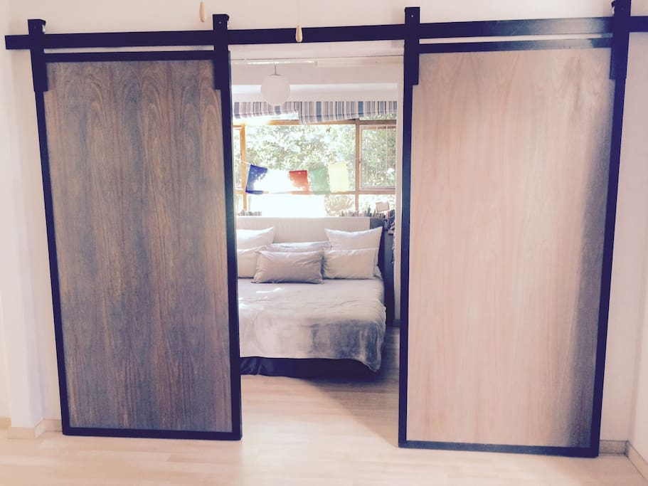 King size bed in bedroom with beautiful barn style doors.