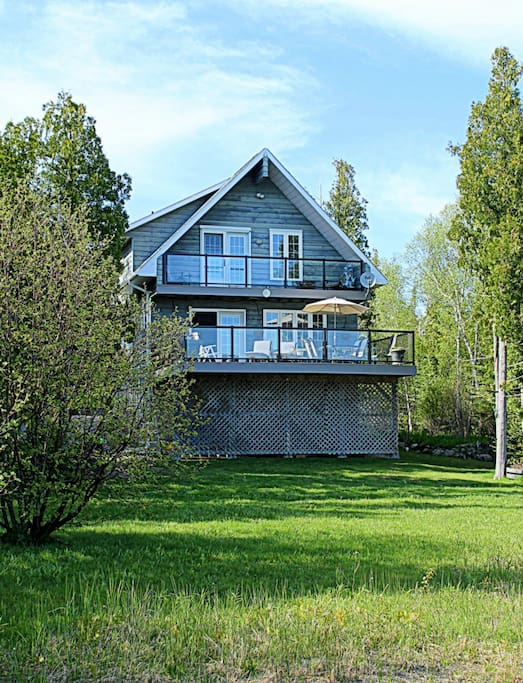 The view of the Willow Bank from the water's edge showing the front lawn and the elevated front deck. The cottage is tucked back into a forest of cedar trees.