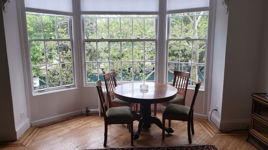 Tons of light with glorious bay window! Eat, read or play among the trees at sunny table; or lower the blinds if it gets too bright!