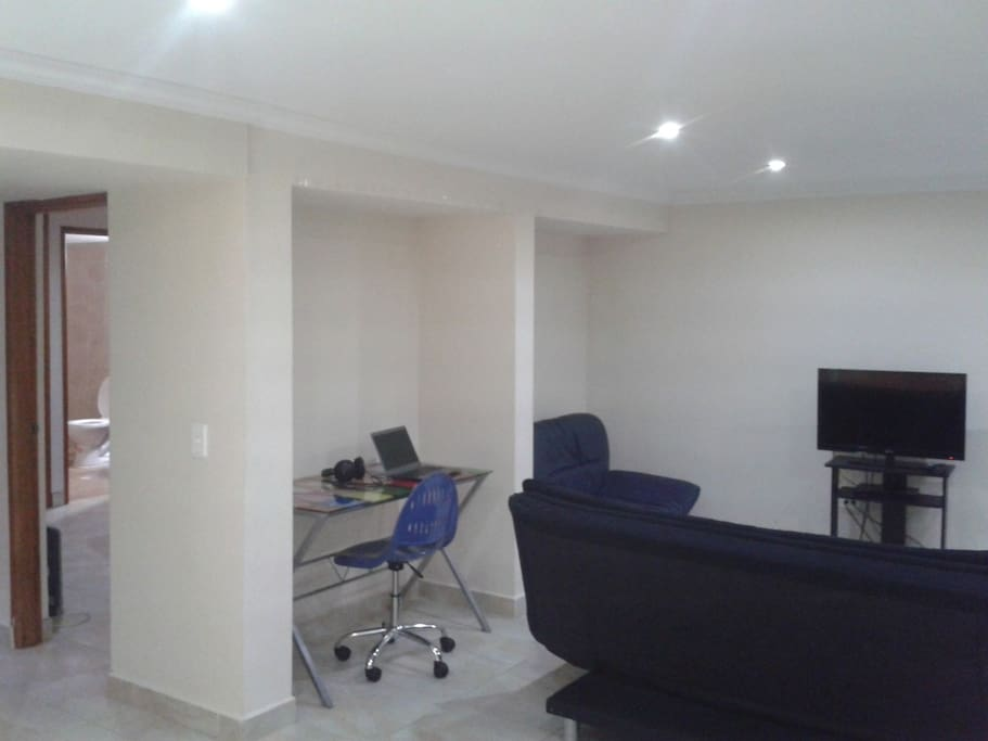 Living area with comfortable sofa, 32 Inch Cable TV, working desk and AC