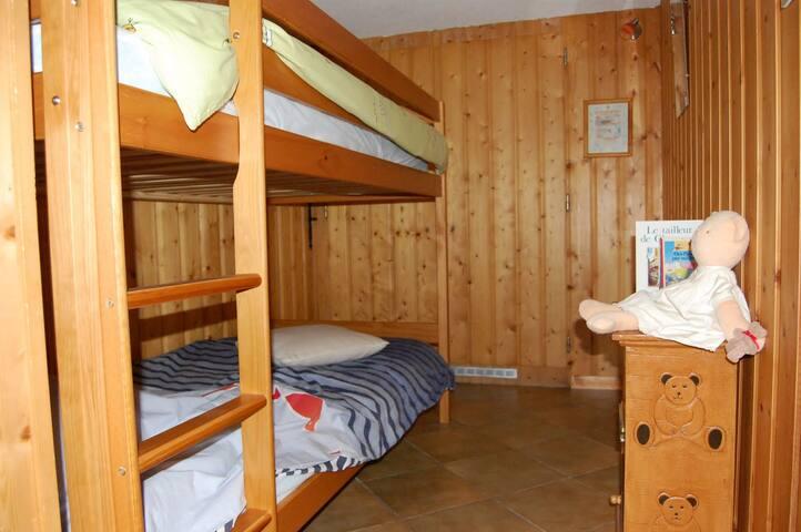 Le coin- enfants avec ses lits superposés. Une armoire murale avec penderie se trouve au fond de la pièce.  Le matériel bébé est fourni à la demande ( lit bébé, transat, chaise-haute, baignoire...)