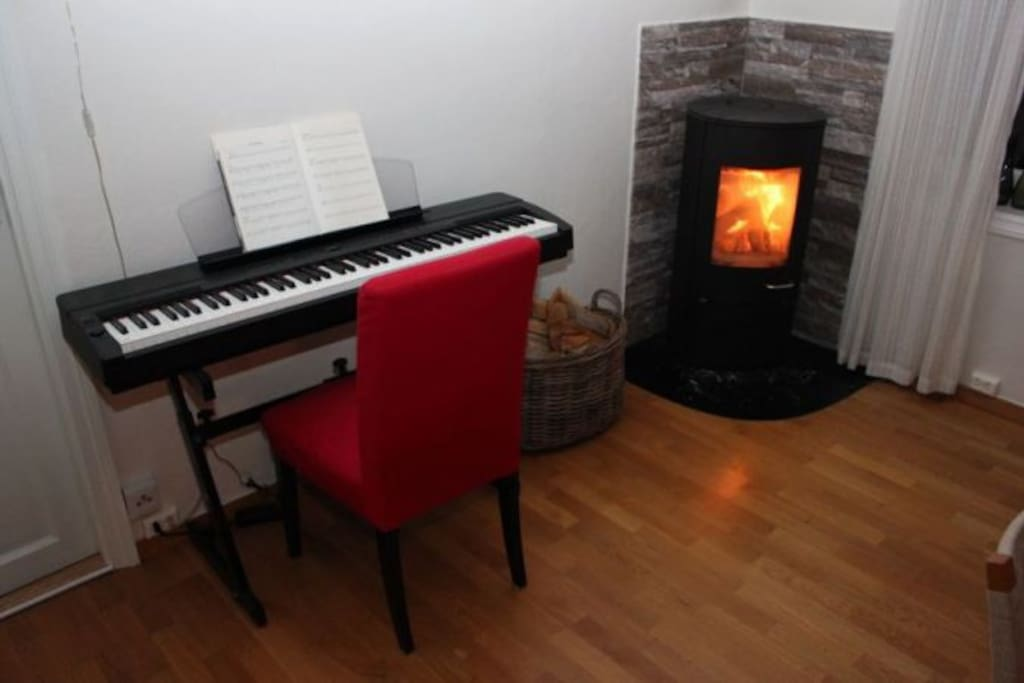 Part of the livingroom with a piano and a fireplace.