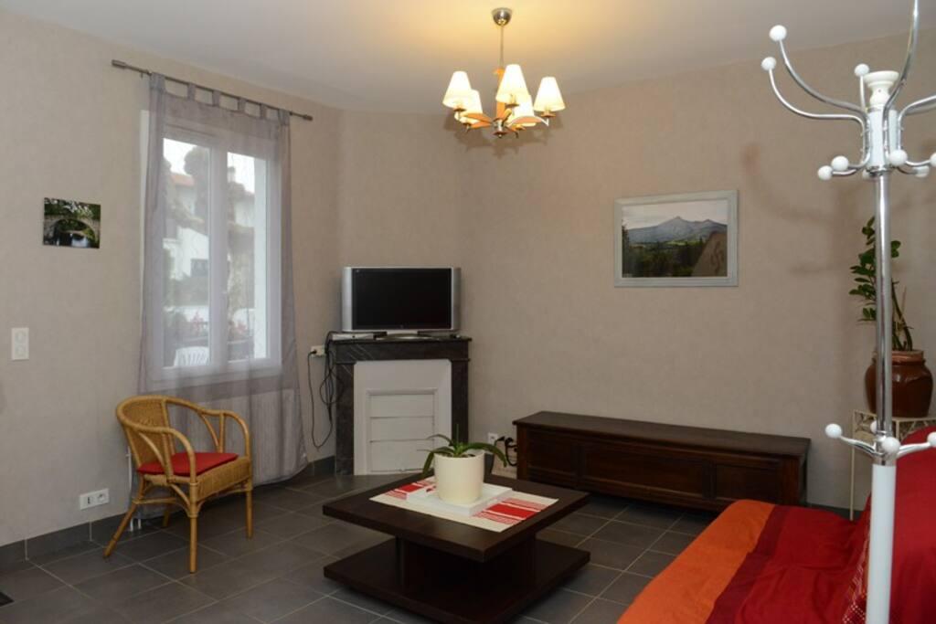 Un salon avec canapé convertible et TV écran plat.