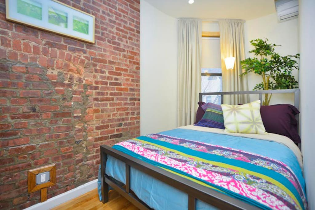 Bedroom with full size bed, original exposed brick wall and window facing the gardens beyond.