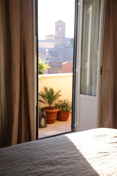 The bell Tower of S. Maria in Trastevere in the morning light, seen from the bed