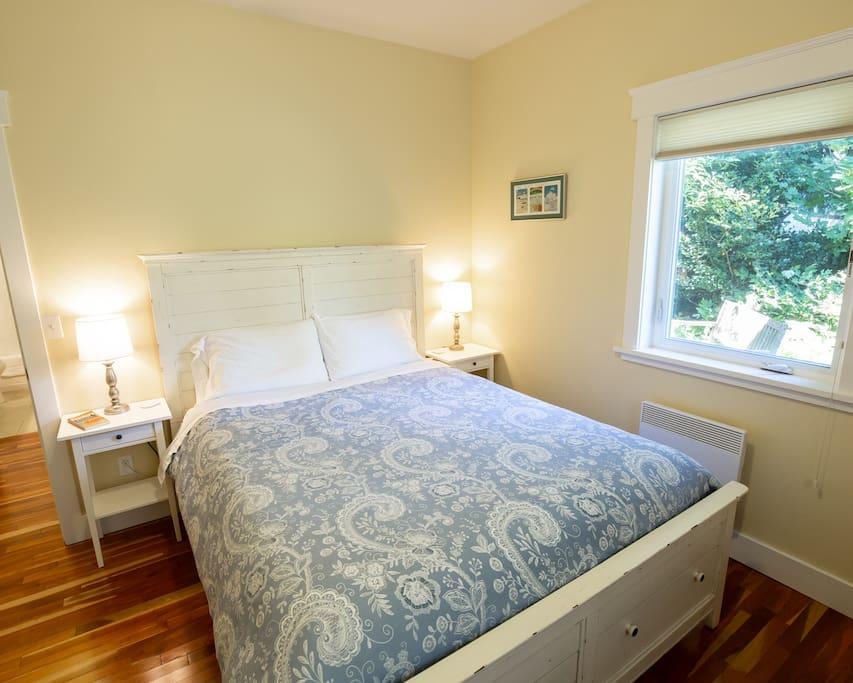 Queen bedroom with window facing back yard.