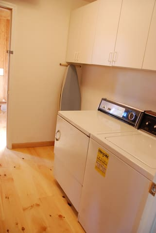 Washer and drier, ironing board and iron in the full-sized laundry room