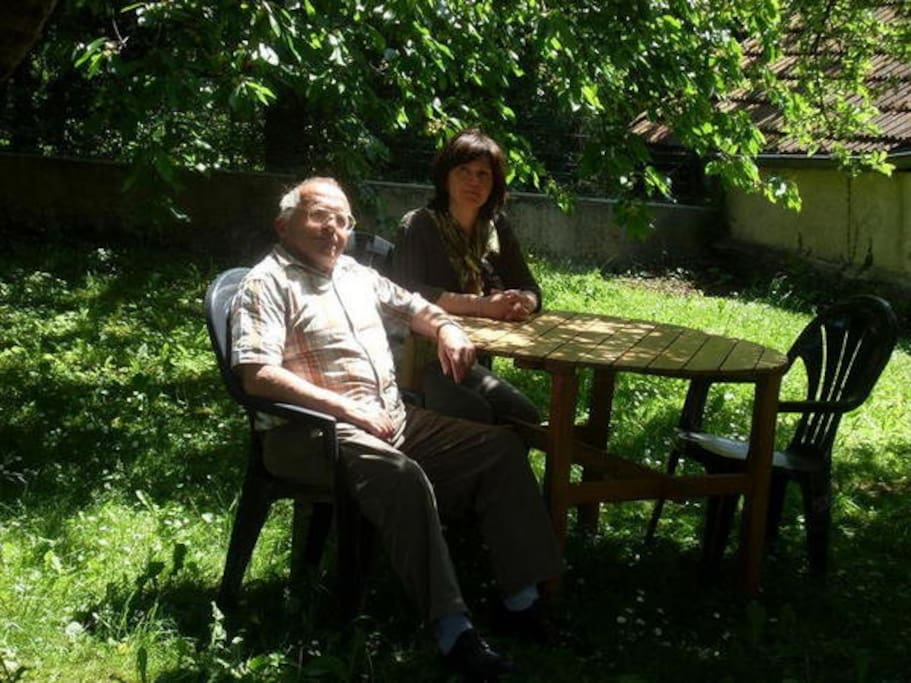 Bernard et Denise assis dans le coin de verdure avec barbecue et salon de jardin / Bernard and Denise sat in the green area with barbecue and garden furniture