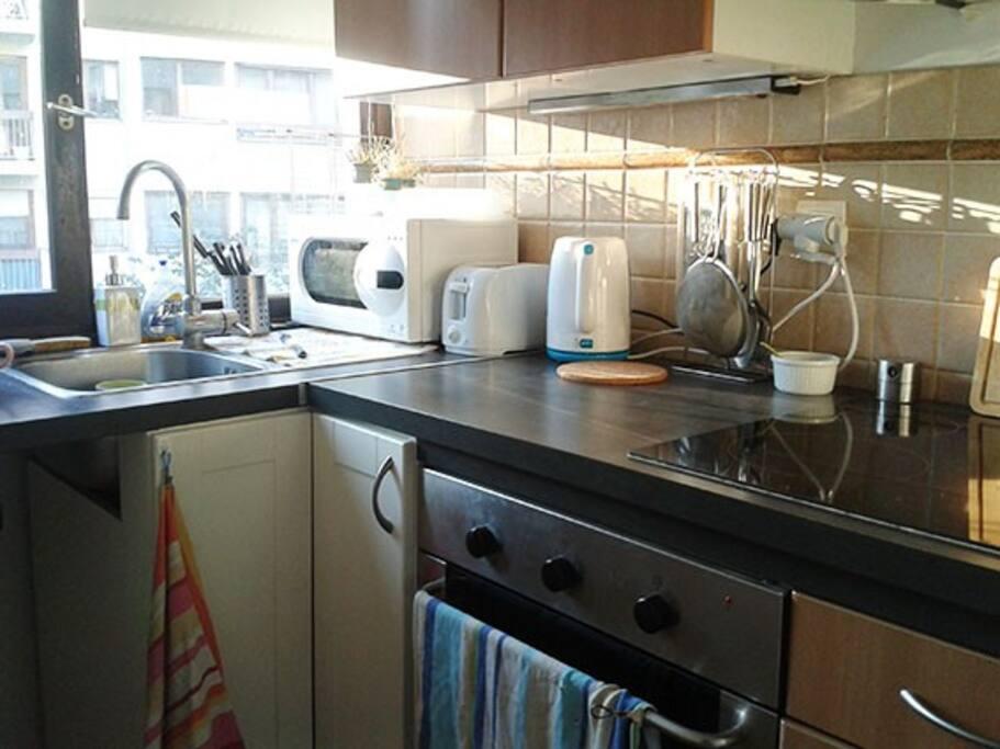 Une cuisine fonctionnelle avec tout ce qu'il faut pour cuisiner.