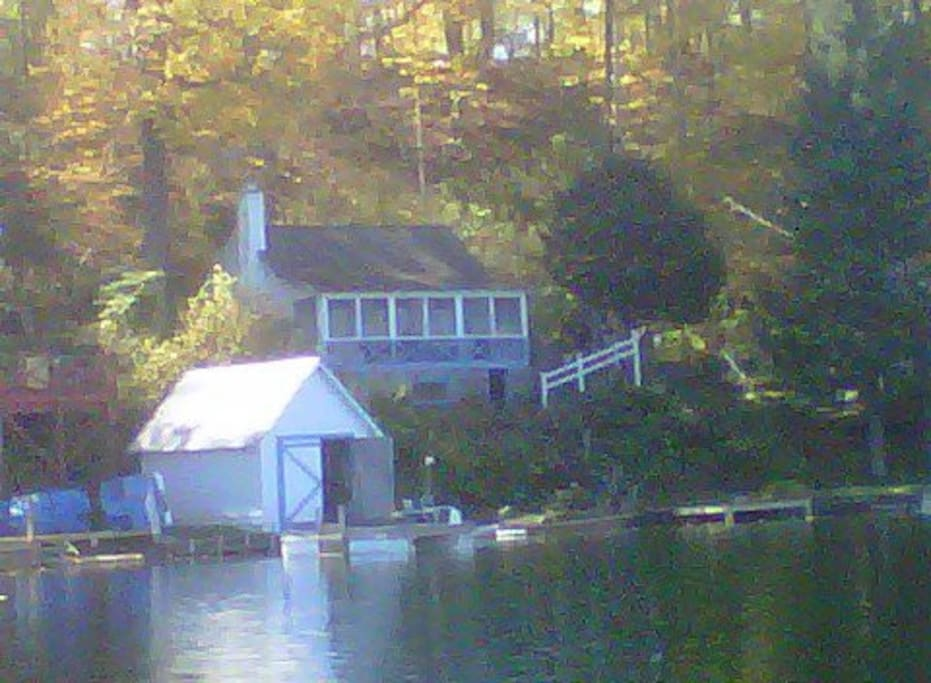 View from the water.  Boat hose, docks, sandy beach and lawn.