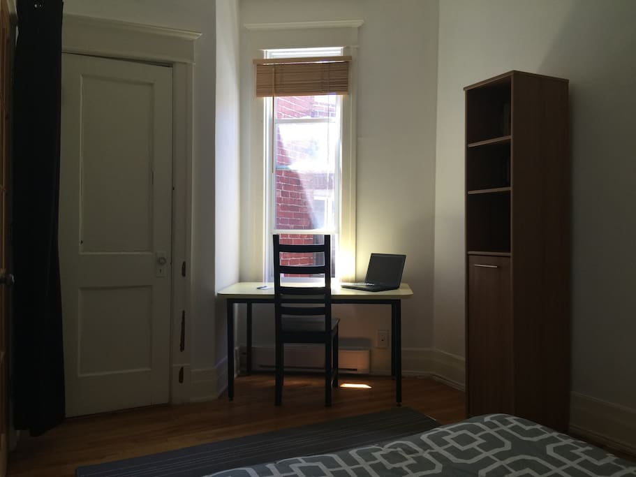 The room is provided with a desk located right by the window which provides great lighting. On the left you can see the door of the walk in dressing / storage space.