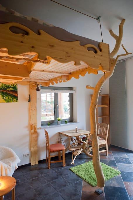 Das Zimmer ist mit Tisch, Stühlen, Sitzecke, Kochecke und einem Doppelbett ausgestattet.