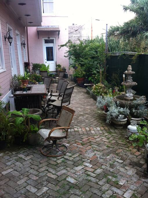 Private courtyard  lush gardens and fountains. Accessible by coded entry gate . Typical of period 1830 New Orleans .