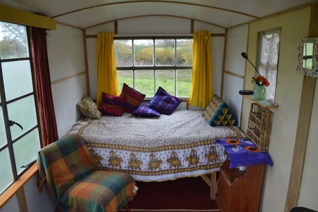 Cosy bedroom in the hut, with a wood stove.