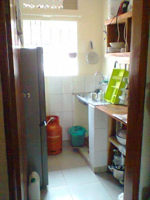 Typical kitchen with fridge, gas cooker, kettle, microwave