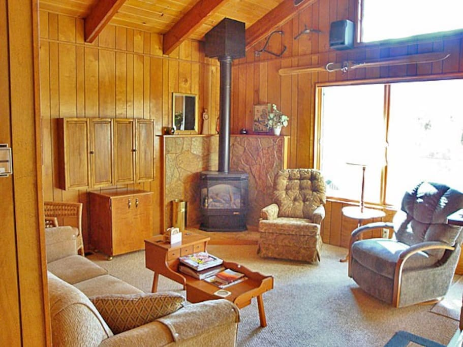 Living room with exposed beam cathedral ceiling and gas fireplace.