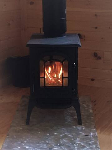 Warmth and light given by the wood stove.