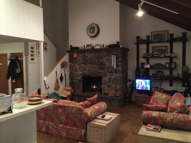 An interior view of the fireplace, open kitchen, living room, and stairs to the second floor.