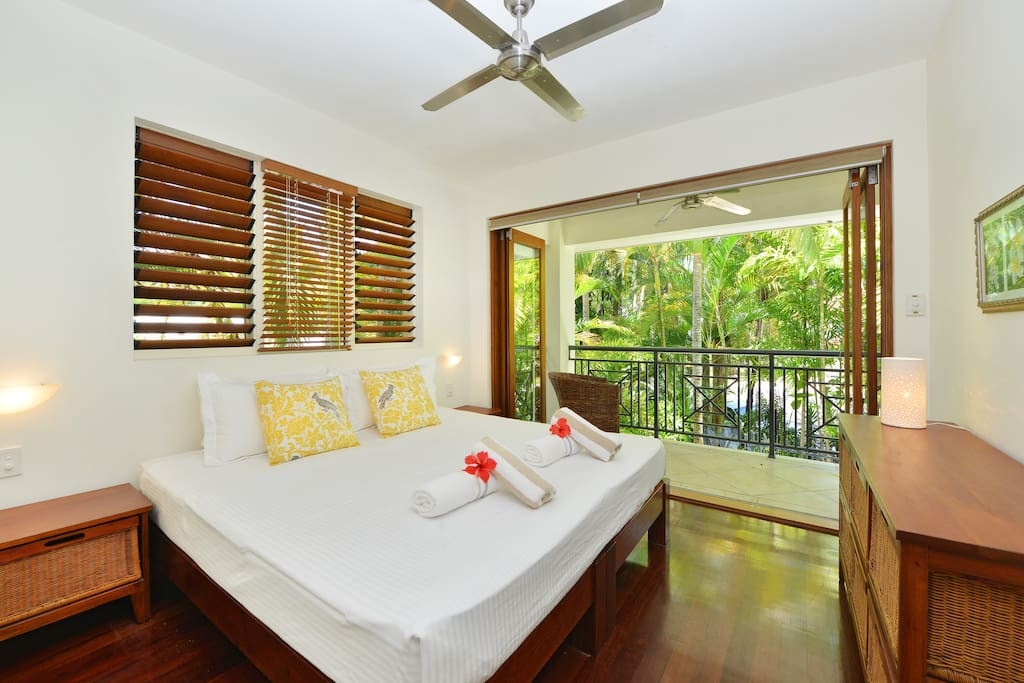 Master bedroom with spa bath and private balcony overlooking pool.