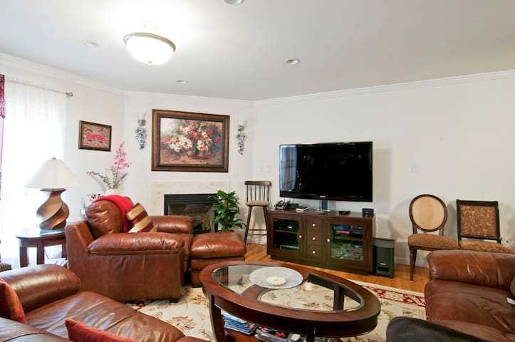 """Watch your favorite movie in 65"""" HD TV, lounging on a real leather arm chair."""